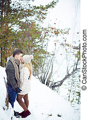 Romantic date - Young amorous couple kissing in winter...