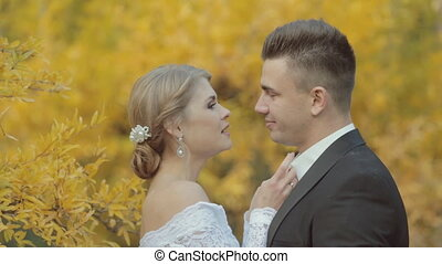 Beautiful bride corrects bow tie groom and they laughing...