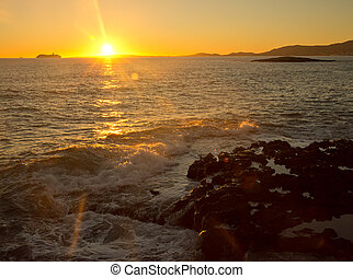 Yellow sunset and waves. Mallorca, Balearic islands, Spain