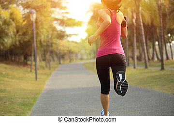 Runner athlete running at tropical park. woman fitness...