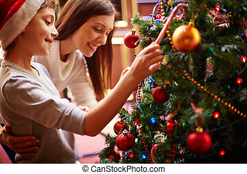 Christmas eve - Cute boy and his mother by Christmas tree