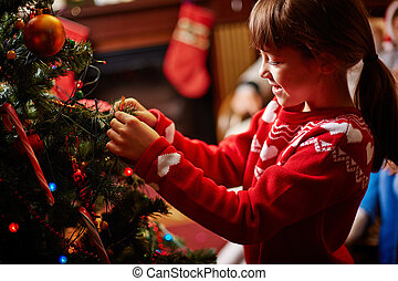 Decorating Christmas tree - Little girl decorating Christmas...