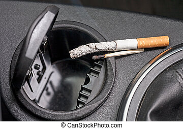 Car ashtray and cigarette - Car ashtray with a smoldering...