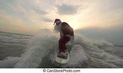 Santa Surfboarding - Sportive Santa Claus balancing on waves...