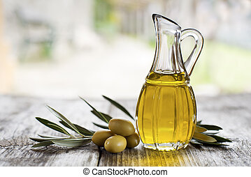 Olive oil and olive branch on the wooden table outside