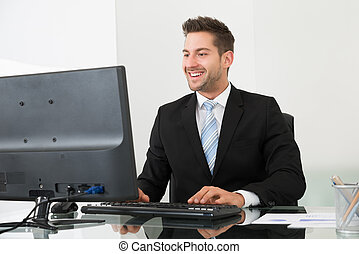 Businessman Using Computer At Desk - Happy young businessman...