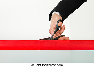 Businessman Cutting Red Ribbon With Scissors - Businessman's...