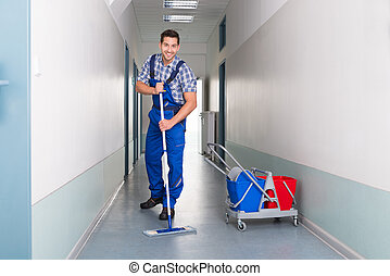 Happy Male Worker With Broom Cleaning Office Corridor - Full...