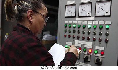 Woman engineer in control room - The workwoman writes the...