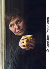 Sad alone Woman Drinking Coffee in Dark Room - Lonely woman...