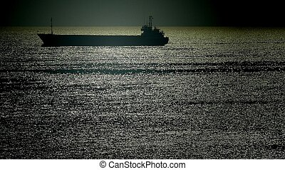 Silhouette of a merchant ship in a twilight sea - Silhouette...