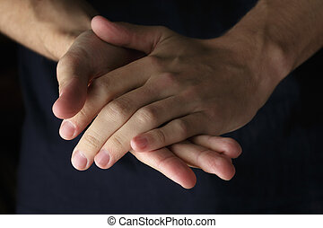 adult man clasped hands, dark style photo