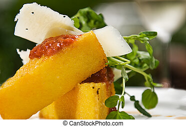 Polenta - A serving of polenta with a tomato sauce, cheese...