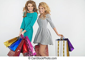 Two blonde holding shopping bags - Two blonde holding...