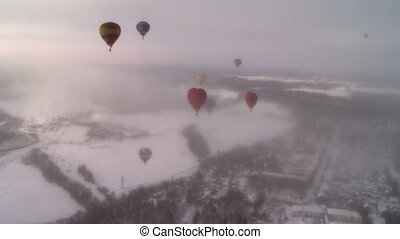 View of hot air balloons flying in dawn mist
