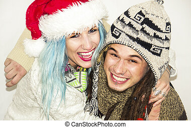 Cute young couple laughing in winter clothes on a white...