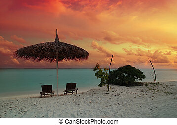 Umbrella and sunset - Umbrella and two chairs on the...
