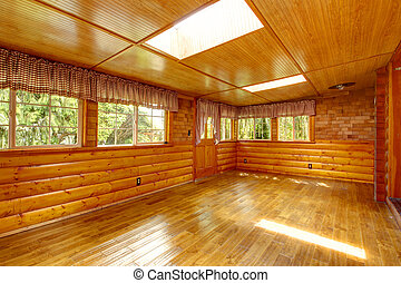 Bright empty log cabin house interior with skylights -...