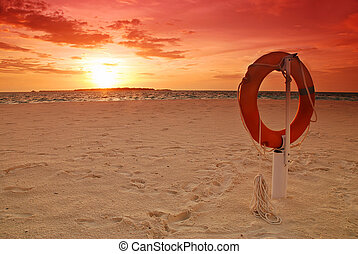 Lifebuoy and sunset - Sunset over the ocean and lifebuoy on...