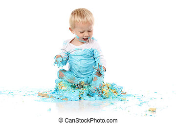 Baby smashing cake - A one year old baby boy smashing a blue...