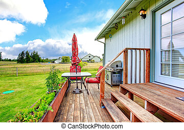 Countryside house exterior with walkout deck and small patio are