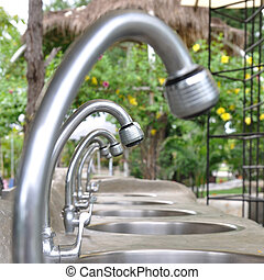 Many water taps and sinks in garden.
