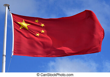 China national flag blowing against blue sky.