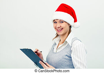 happy girl in santa hat with a notebook