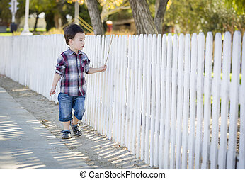 Young Mixed Race Boy Walking with Stick Along White Fence -...
