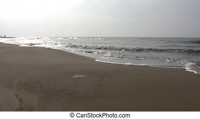 Beach in autumn - Low angle shot of sea water soaking into...