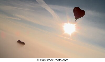 Hot air balloon heart-shaped flying in dawn mist - View of...