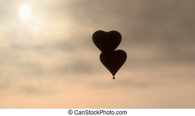 Two air balloons heart-shaped flying in dawn haze - Two hot...