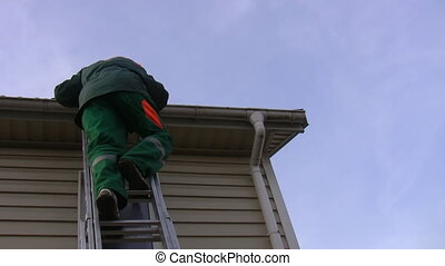 Man climbs down ladder - Man in a green contractor uniform...