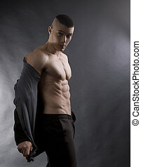 Young sexy man with athletic body on black background -...