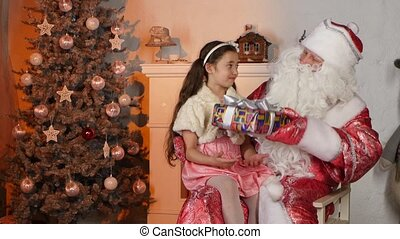 Little beautiful girl getting present from Santa Claus. Looking happy and surprise with Christmas tree on background