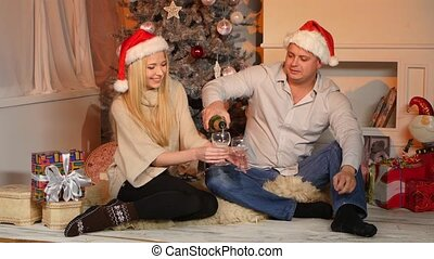 Young happy couple holding pours glasses with champagne at floor near Christmas tree