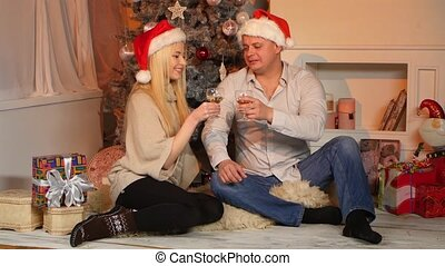 Young happy couple holding glasses with champagne at floor near Christmas tree