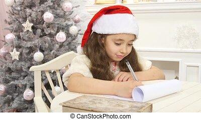 Pretty girl in Santa hat writes letter to Santa near...