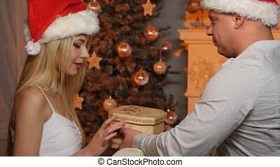 Young man gives a present to his girlfriend for Christmas