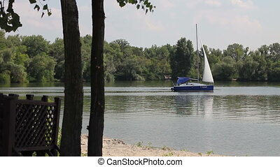 sailboat on the river - Sailboat floats on the river leaving...