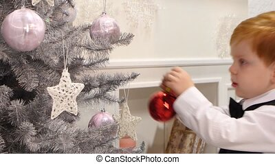 Happy smiling little boy decorated new year tree red ball