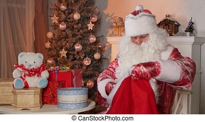 Santa Claus putting gifts in bag isolated near the christmas tree