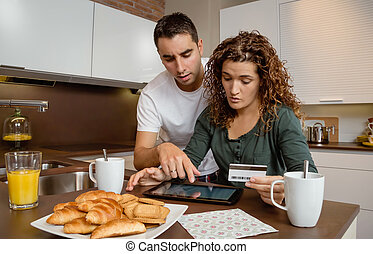 Couple with electronic tablet reviewing credit card payouts...
