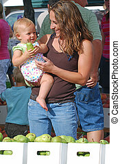 Mother and daughter at farmer\'s market. - Young mother and...