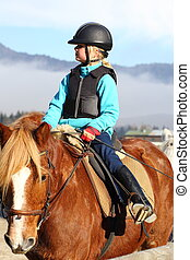 going on horseback - young girl is going on horseback in...