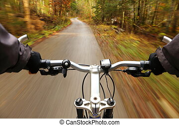 man on bicycle is driving fast in forest