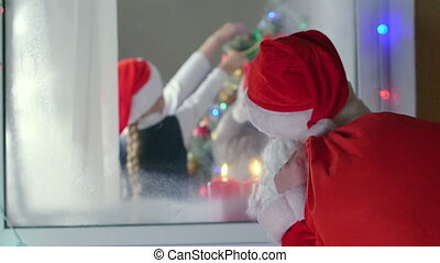 Santa Claus knocking at window and looking into the house at...