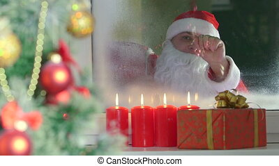 Santa Claus knocking at window - Smiling father dressed as...