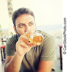 Young man drinking beer sitting at the restaurant near the...
