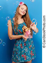 Pretty girl with barbie on blue background